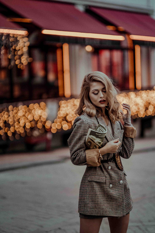 người phụ nữ mặc áo khoác dài cầm báo
