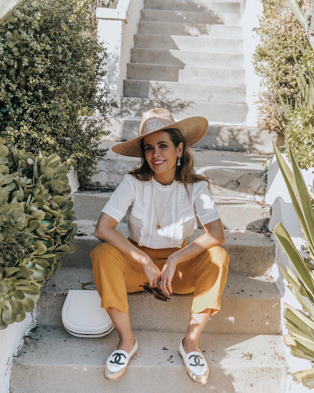Bộ trang phục mùa hè xinh xắn và cổ điển với sơ mi trắng, quần vàng, giày lười trắng, mũ rộng vành và dây chuyền dáng dài làm điểm nhấn.