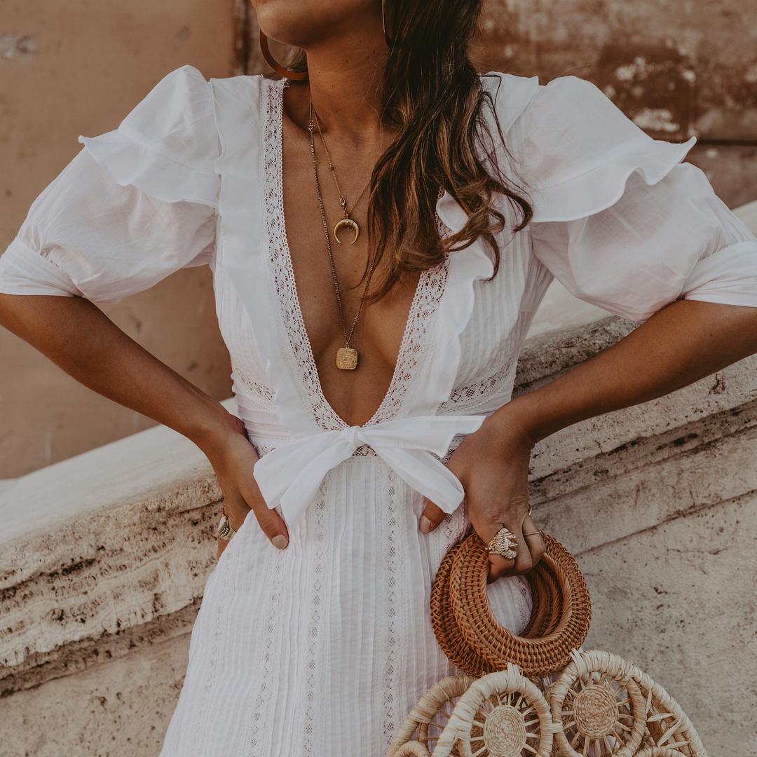 Dây chuyền vàng nhiều lớp tạo điểm nhấn cho bộ trang phục Bohemian với đầm trắng và túi cói