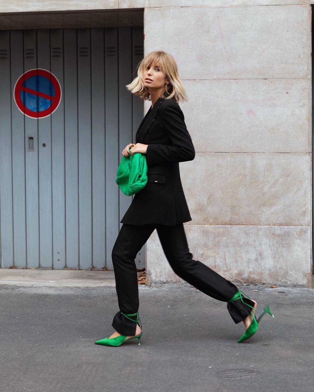 cung Bạch Dương mặc âu phục đen với giày và túi xanh lá