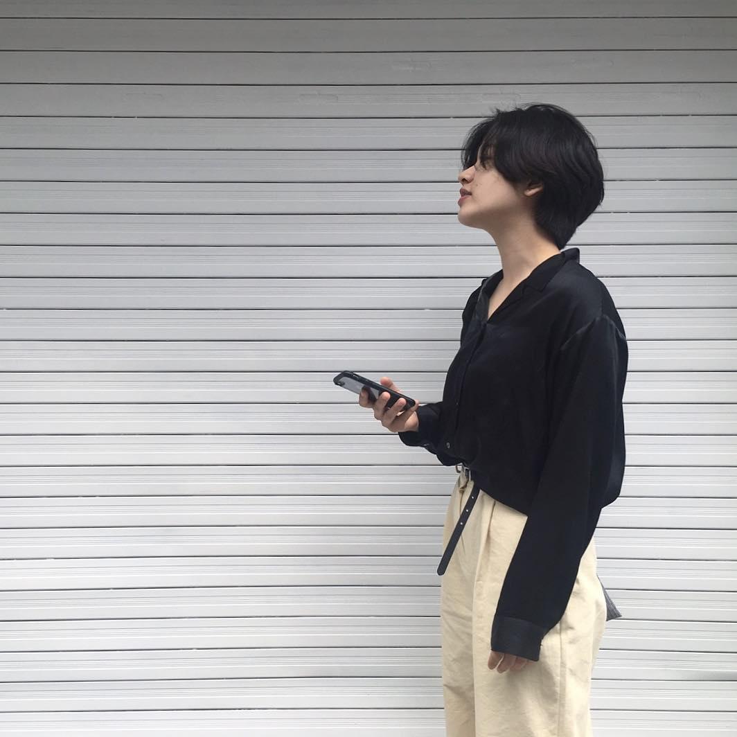 Nữ diễn viên Lee Joo Young của Itaewon Class trong street style đời thường với áo sơ mi satin màu đen và quần khakis