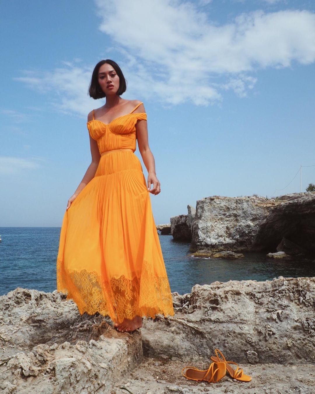 Fashionista Tiffany Hsu diện đầm voan dài màu vàng nổi bật khi đi biển