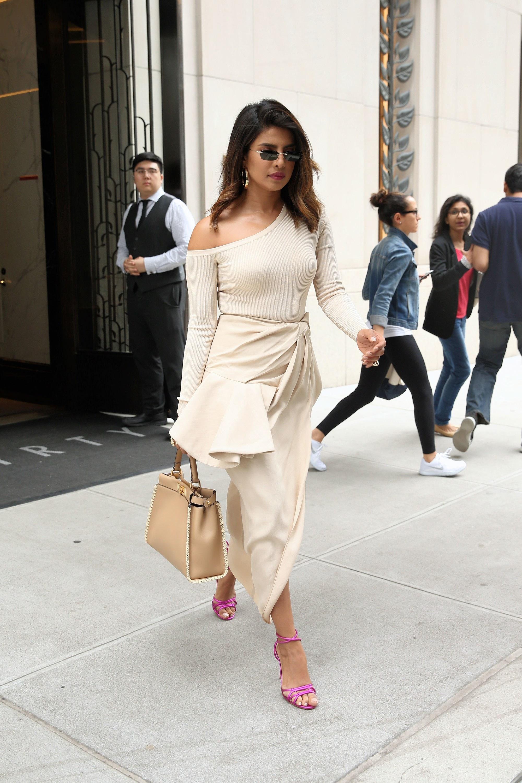 Cách mặc đẹp như Priyanka Chopra với áo lệch vai và chân váy bất đối xứng màu kem, giày sandals cao gót hồng