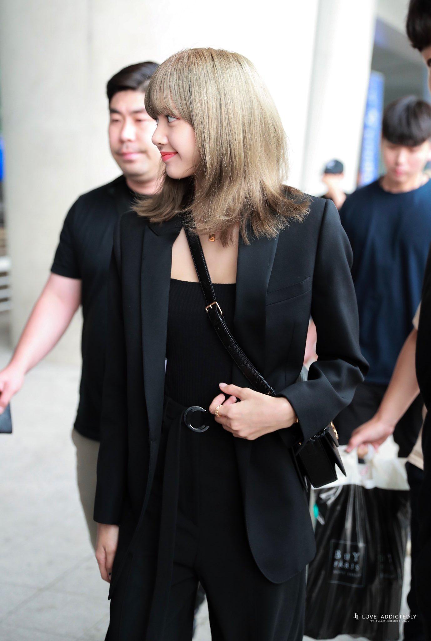 """Lisa diện """"cây"""" đen với blazer, áo thun và quần âu tại sân bay"""