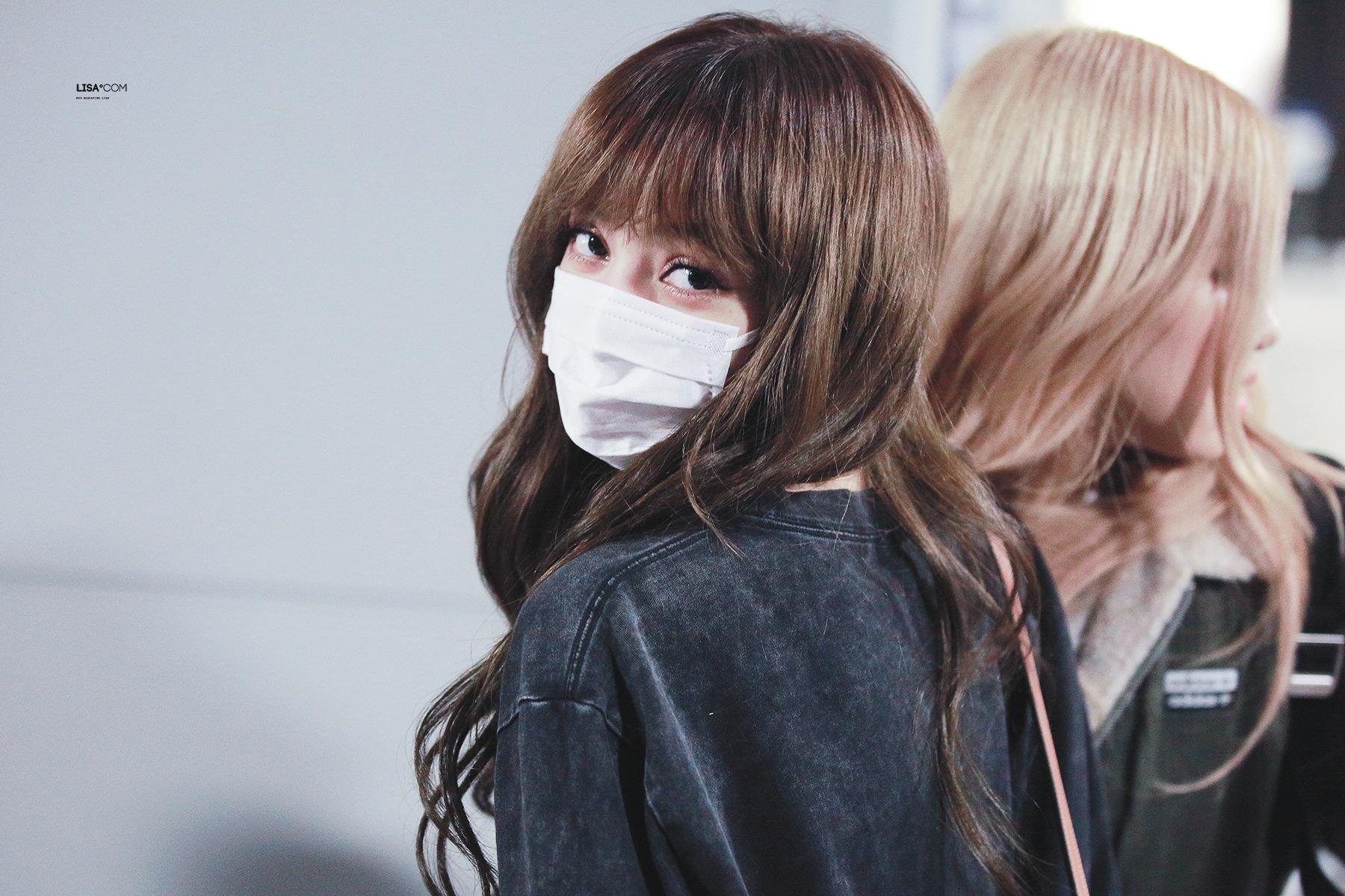 Lisa đeo khẩu trang ở sân bay
