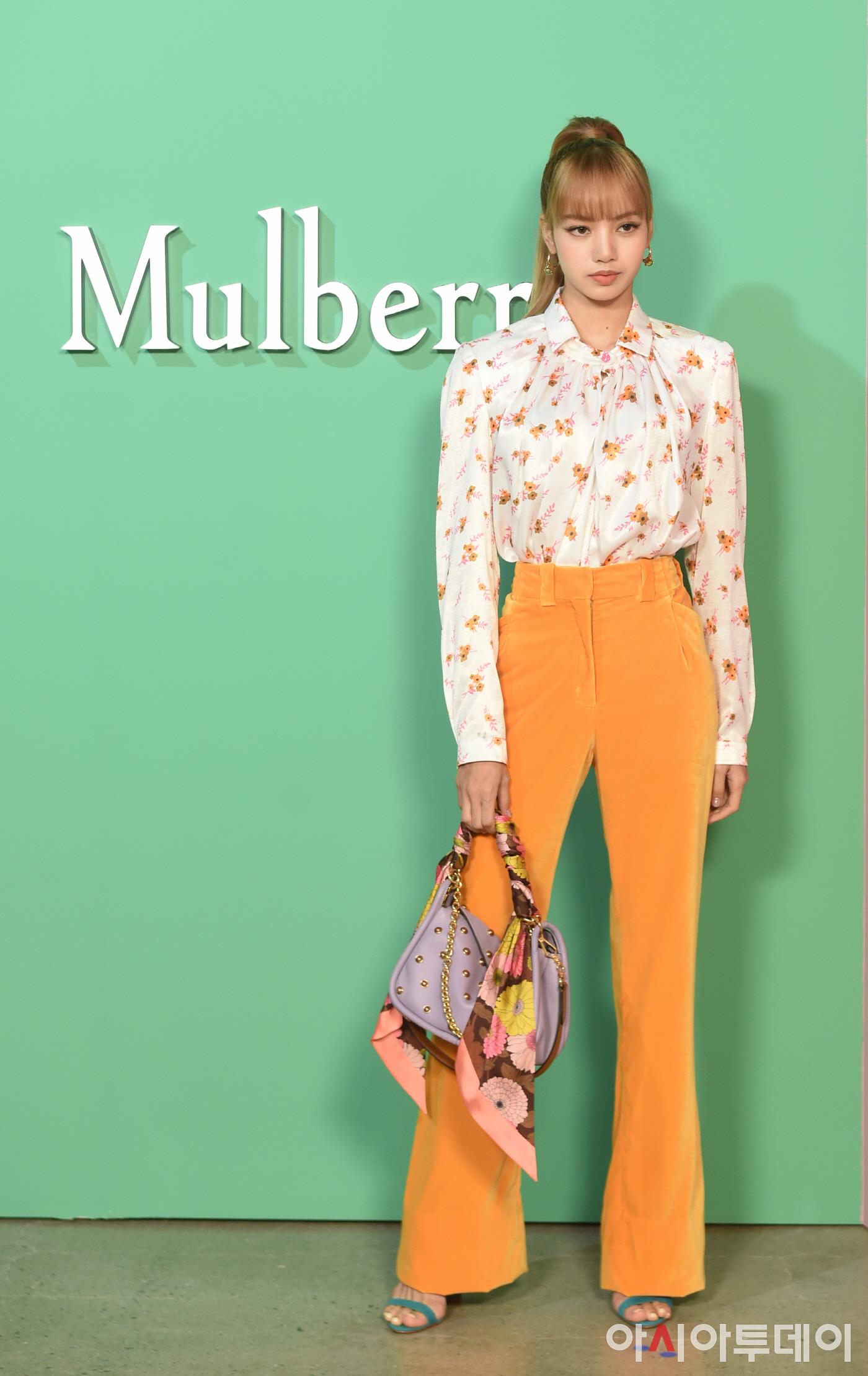 Lisa mặc áo hoa, quần ống loe vàng và túi xách thắt khăn tại buổi trình diễn BST Thu - Đông 2018 của Mulberry