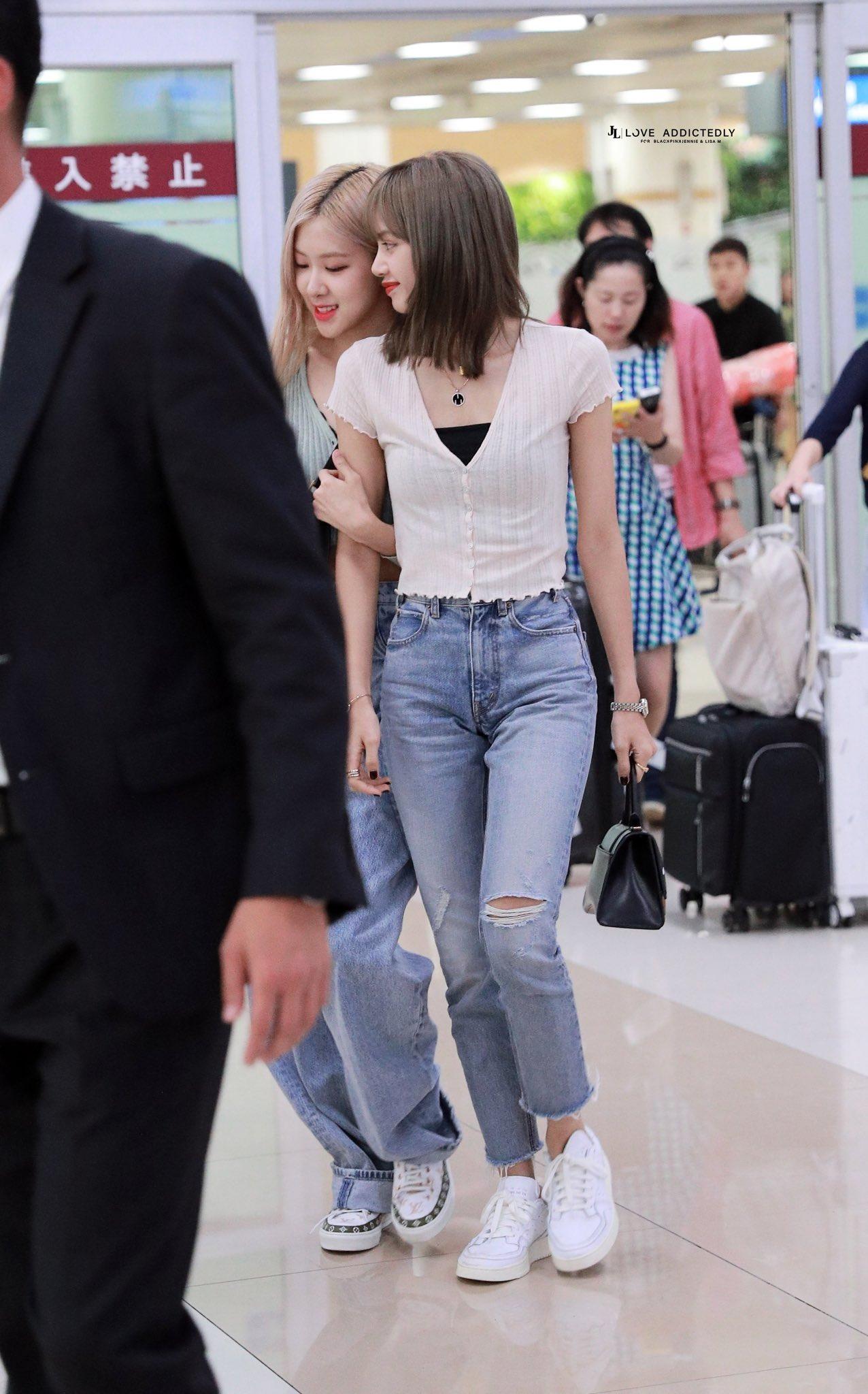 Lisa mặc áo dệt kim ngắn tay và quần jeans rách tại sân bay