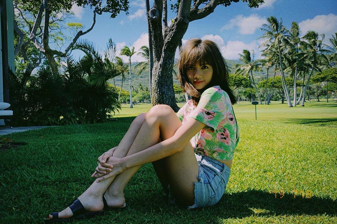 Lisa mặc áo in hoa và quần shorts jeans