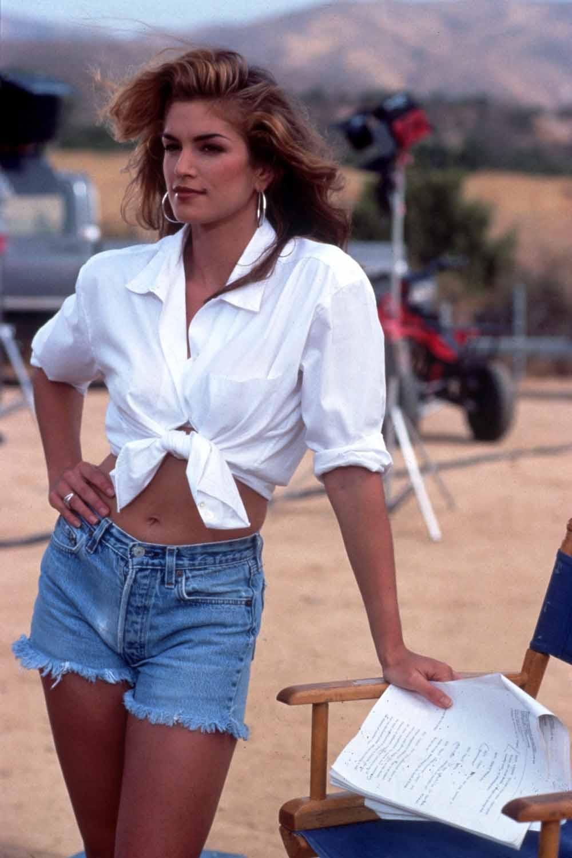 Cindy Crawford năm 1992 mặc áo sơ mi trắng buộc vạt và quần shorts jeans