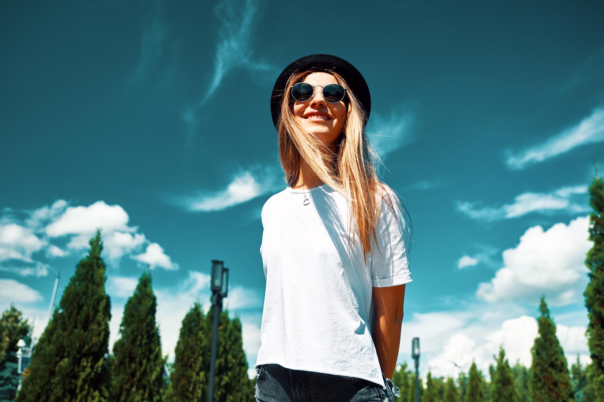 cô gái mặc áo thun trắng đội mũ phớt đeo kính râm
