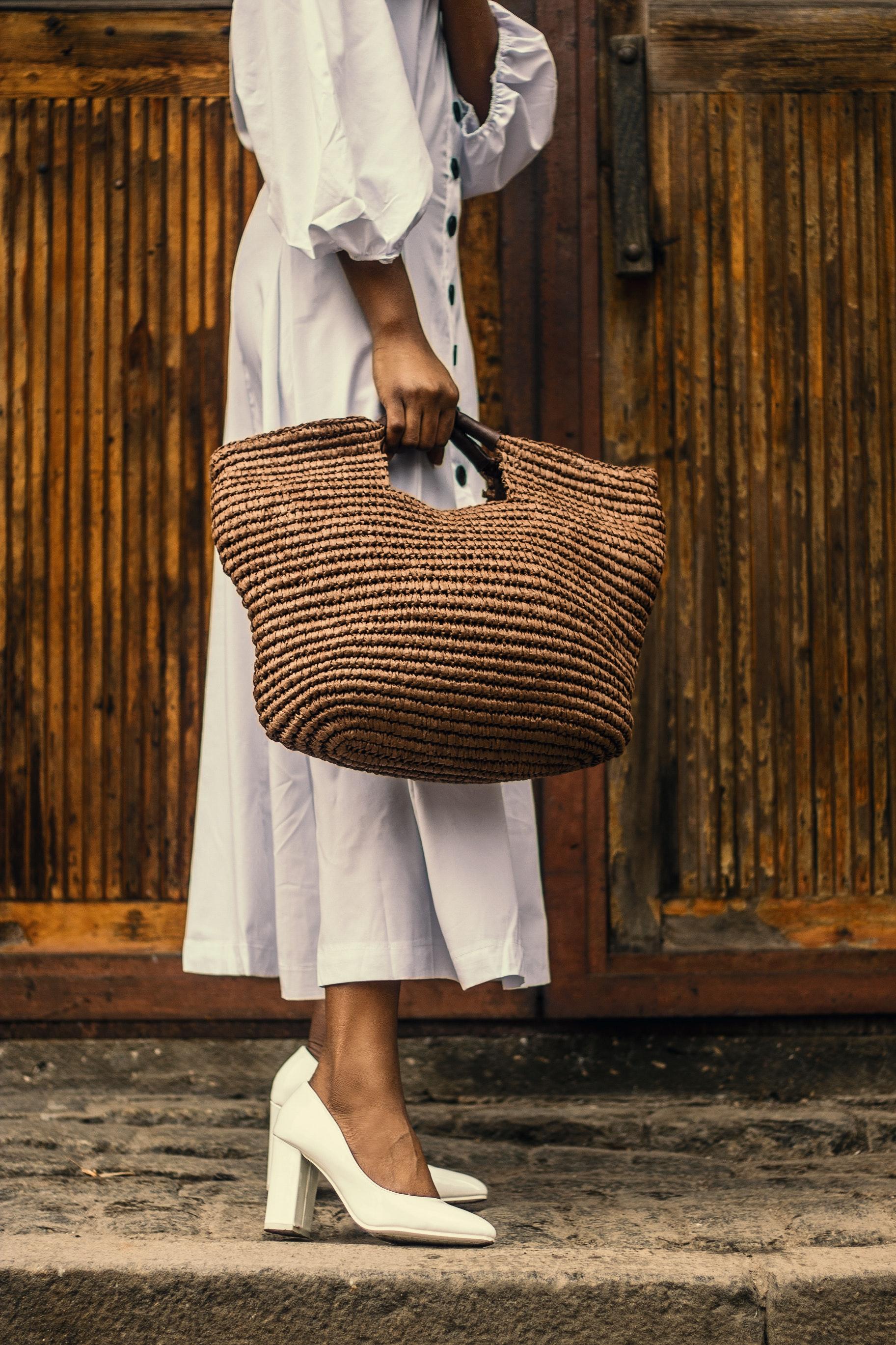 cô gái mặc đầm trắng dài mang giày cao gót vuông và túi xách đan cói
