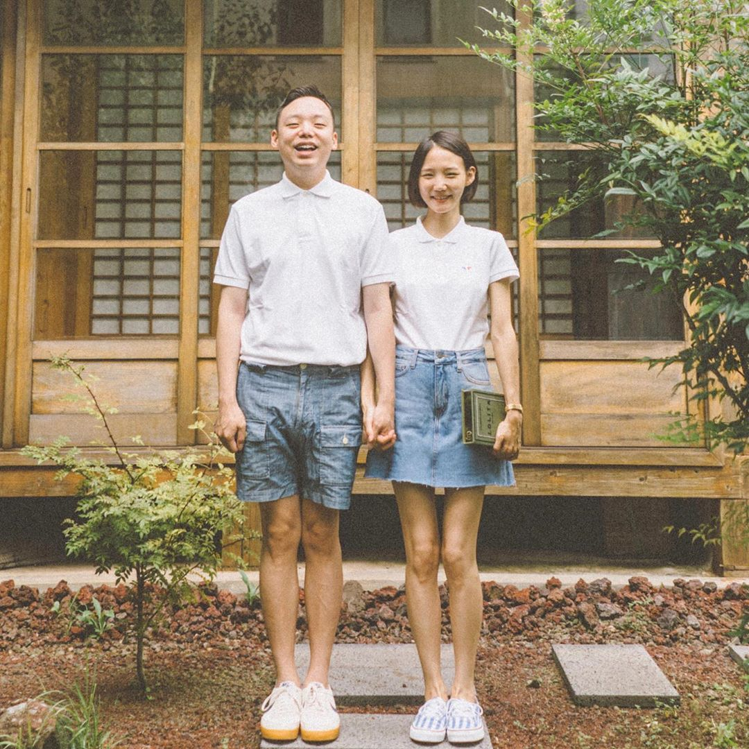 Cặp đôi mặc áo thun cổ bẻ màu trắng đứng trước hiên nhà