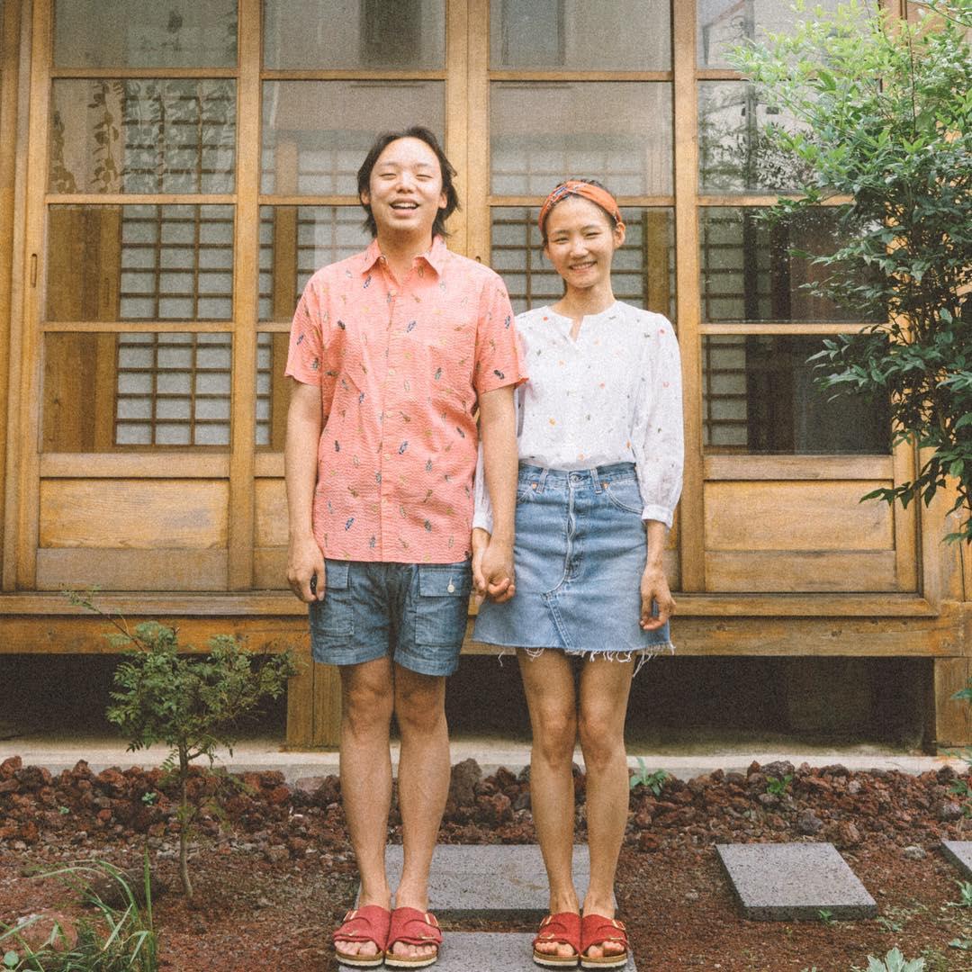 Cặp đôi mặc áo sơ mi in họa tiết đứng trước hiên nhà