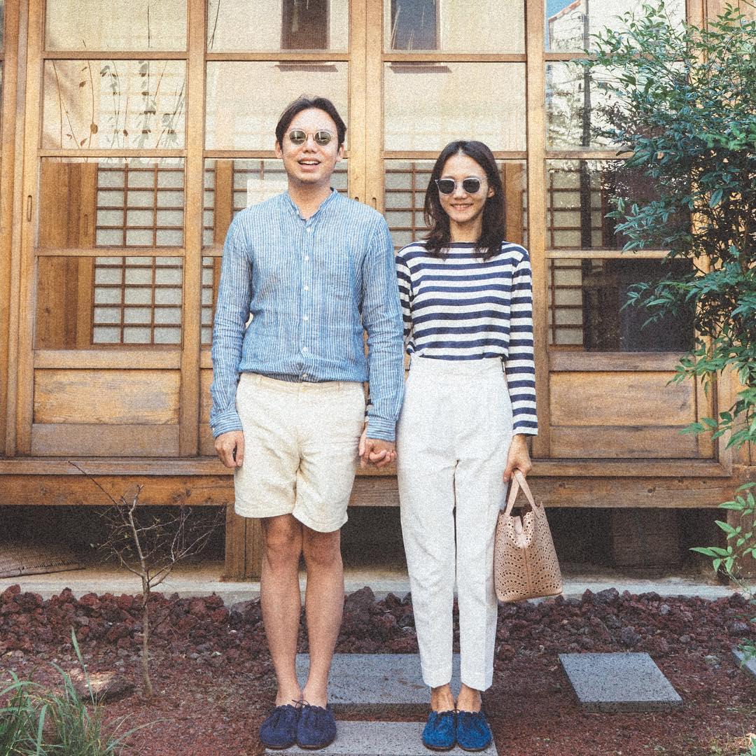 Cặp đôi diện đồ phong cách thủy thủ nắm tay chụp ảnh trước hiên nhà
