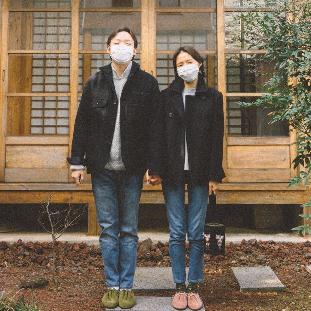 Cặp đôi mặc áo khoác, đeo khẩu trang chụp ảnh trước hiên nhà