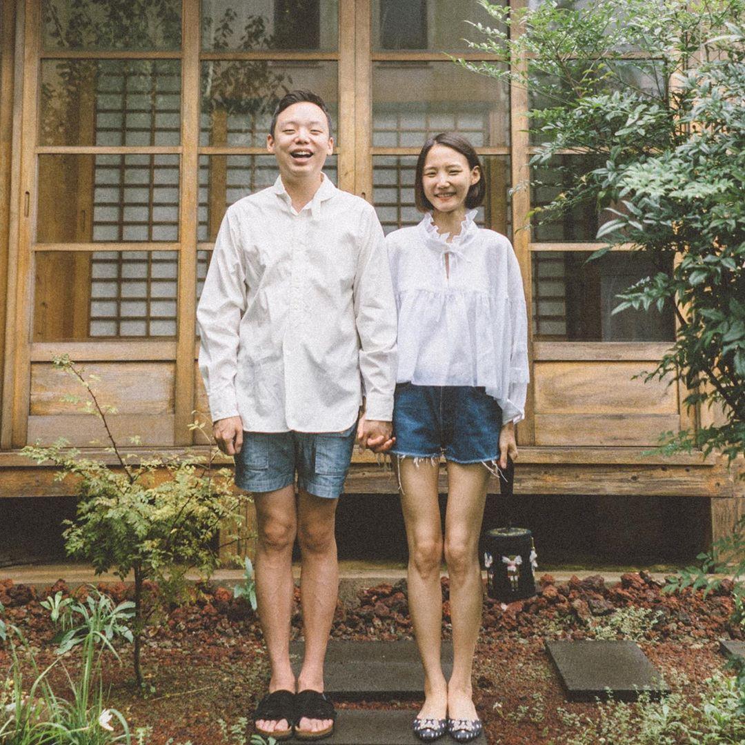 Cặp đôi mặc sơ mi trắng và quần shorts jeans chụp ảnh trước hiên nhà