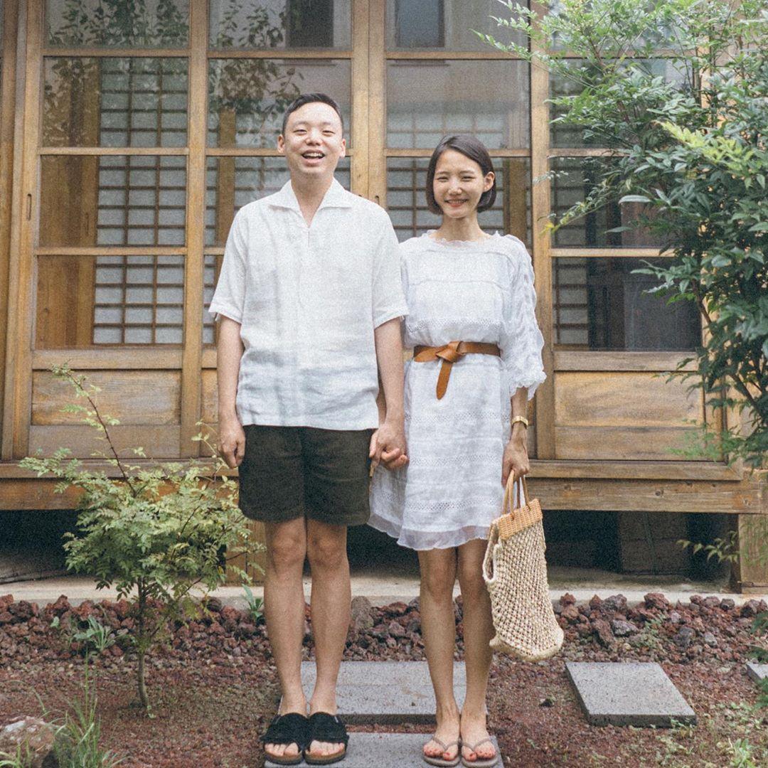Cặp đôi mặc đồ màu trắng nắm tay chụp ảnh trước hiên nhà