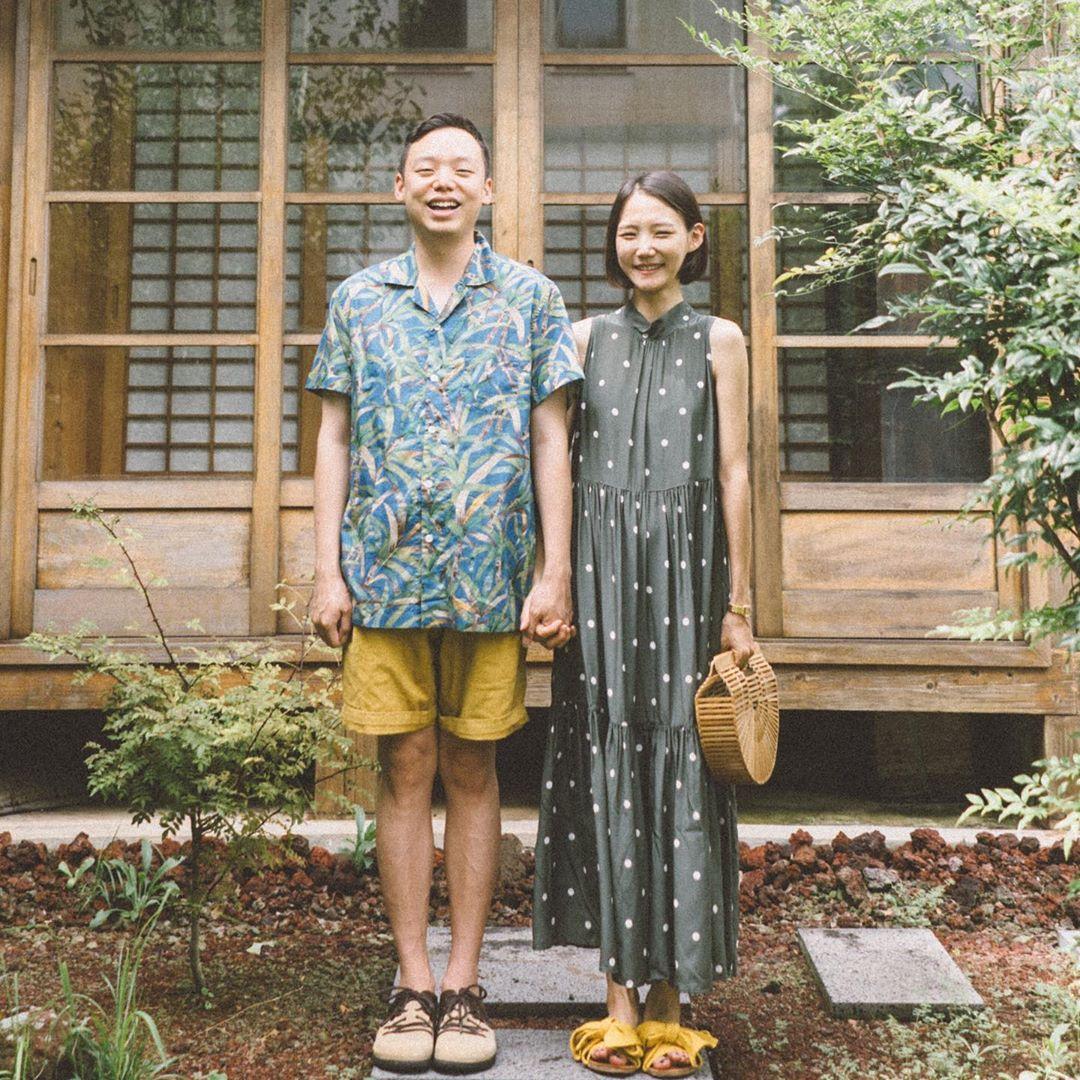 Cặp đôi mặc đồ in họa tiết nắm tay chụp ảnh trước nhà