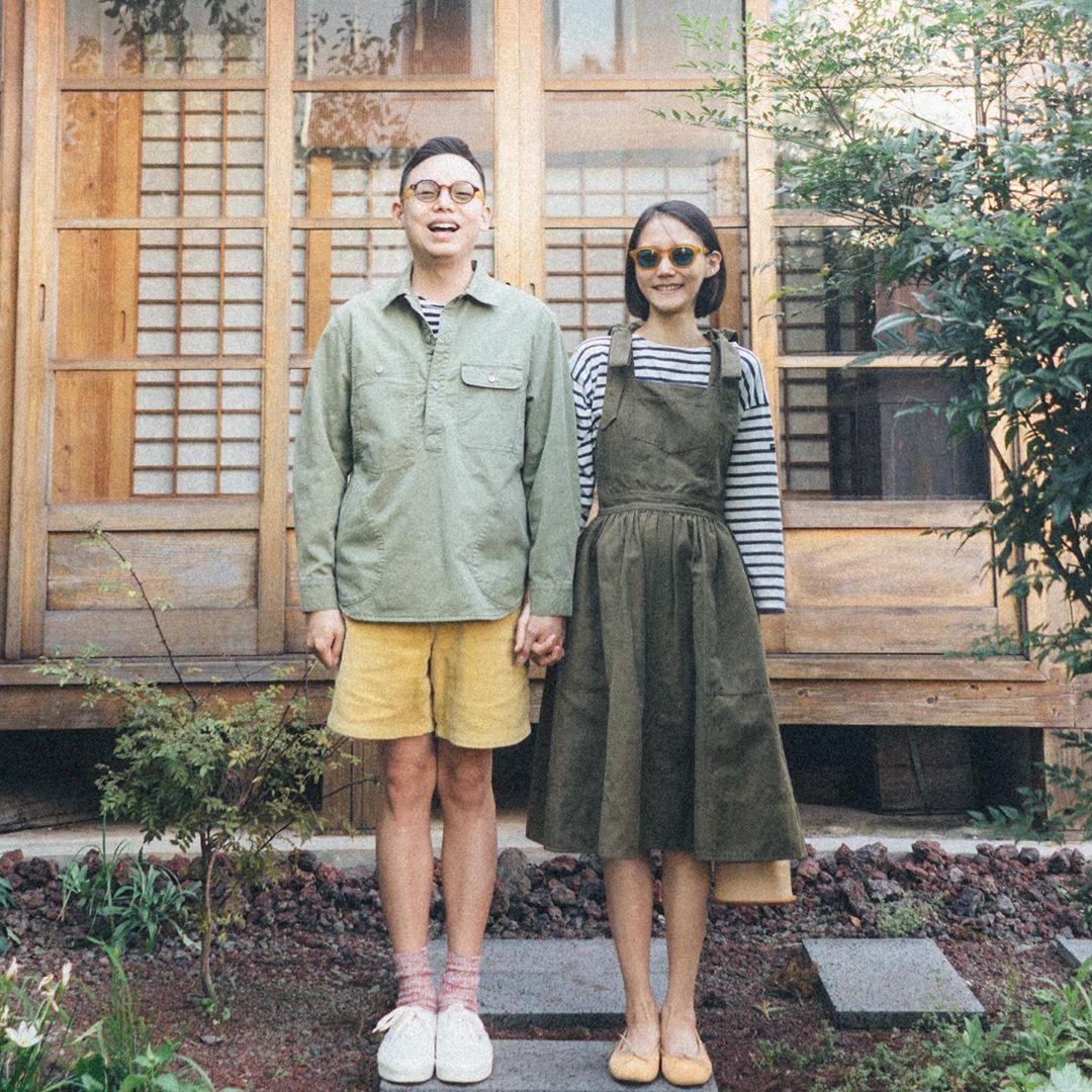 Cặp đôi mặc đồ màu xanh olive cầm tay nhau chụp ảnh trước hiên nhà