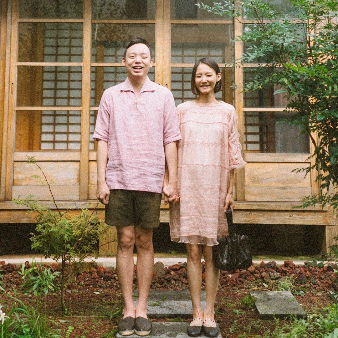 Cặp đôi mặc đồ màu hồng nhạt nắm tay đứng trước nhà