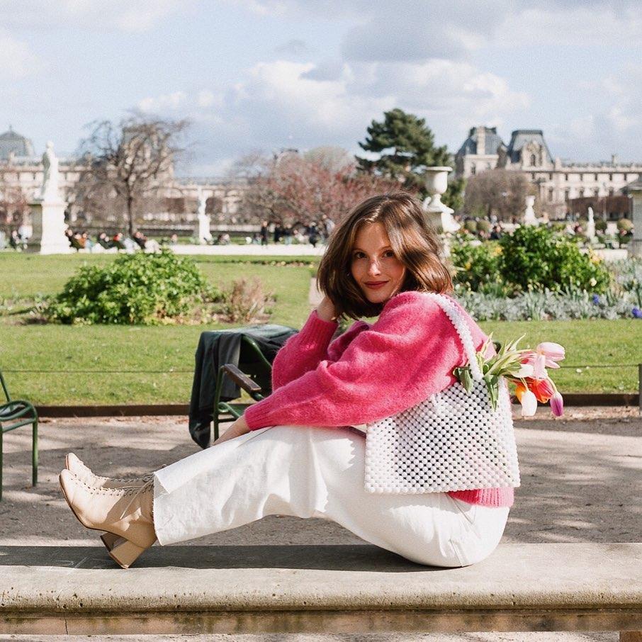 Tín đồ thời trang Pháp Camille Yolaine mặc áo len hồng, quần trắng, đeo túi ngọc trai, mang giày cao gót