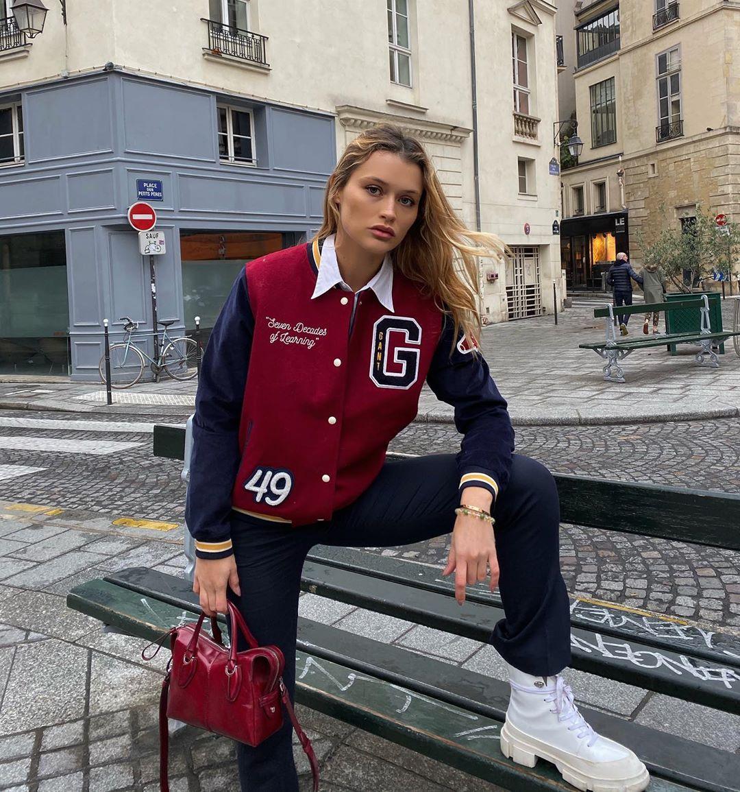 Tín đồ thời trang Pháp Chloe Careux mặc áo khoác bóng chày đỏ-xanh, mang giày bốt trắng