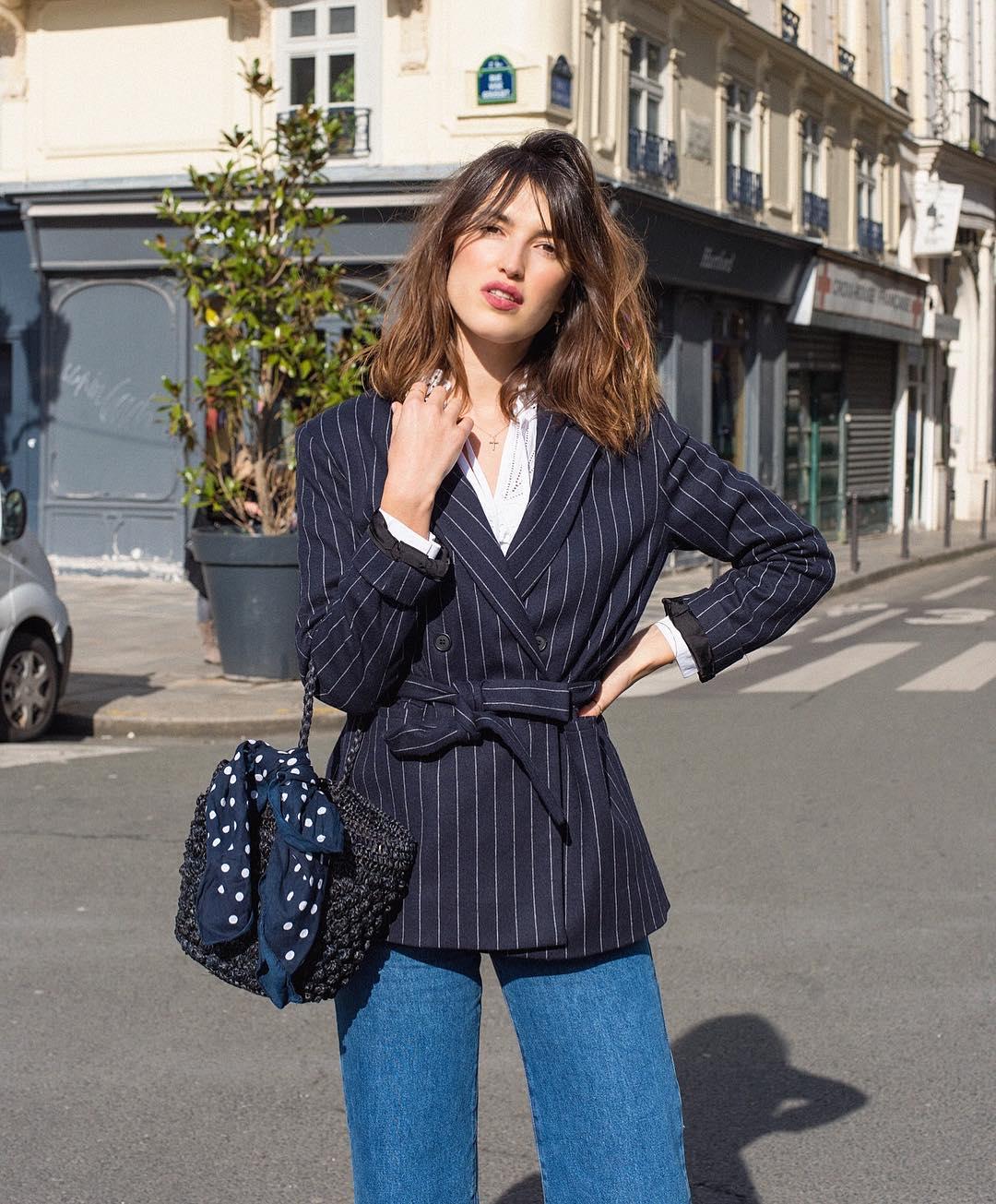 Thời trang Pháp của Jeanne Damas với áo blazer sọc, quần jeans, đeo túi cói đen