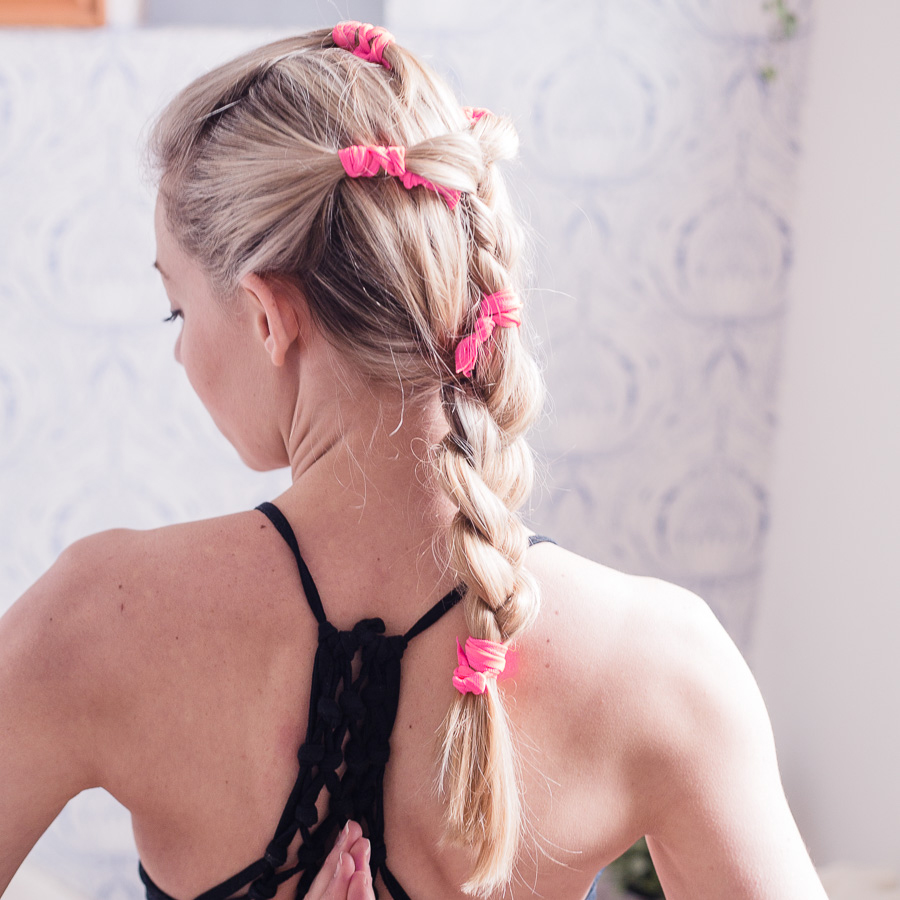 Cô gái tết tóc bằng dây vải màu hồng để tập Yoga