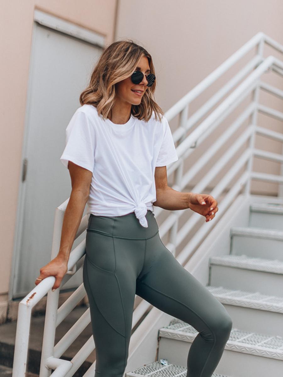 Cô gái mặc đồ tập Yoga với áo thun trắng và quần leggings xám