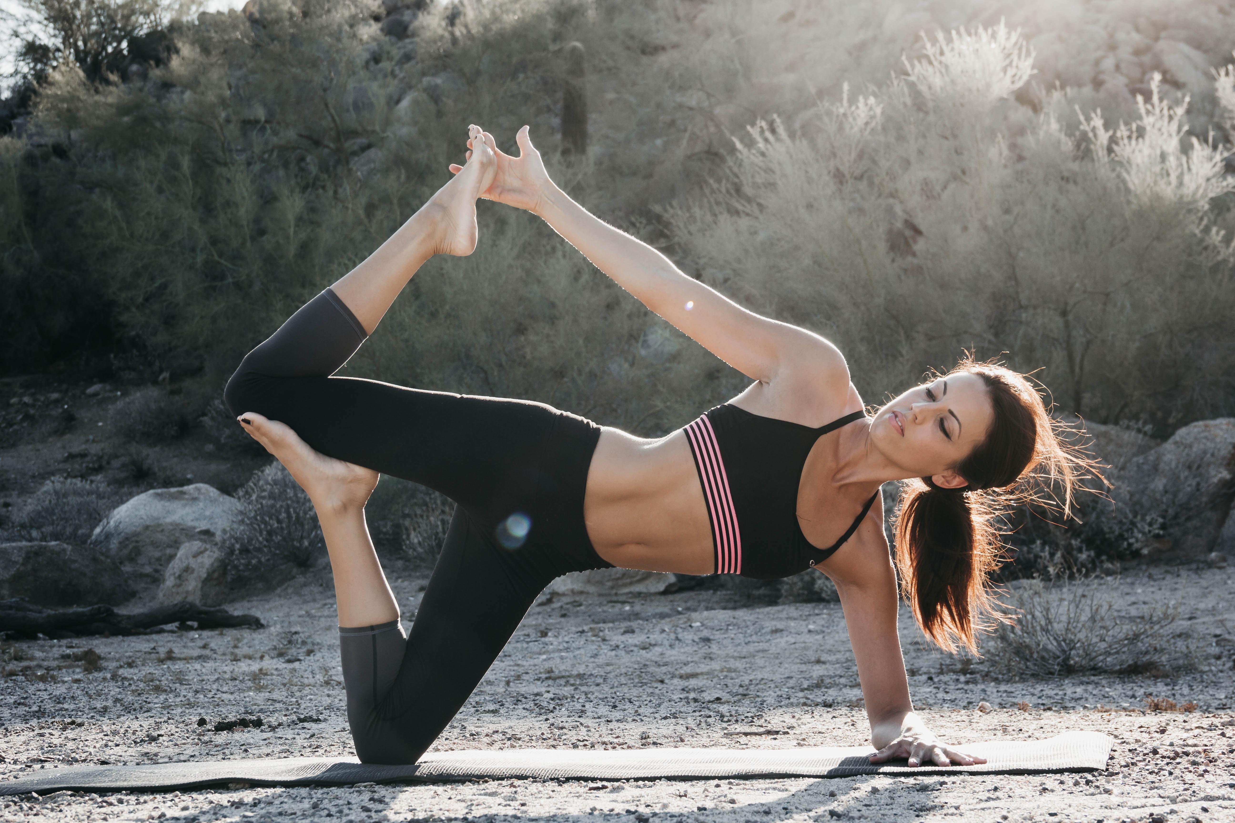 Cô gái mặc đồ tập Yoga màu đen đang luyện tập ngoài trời
