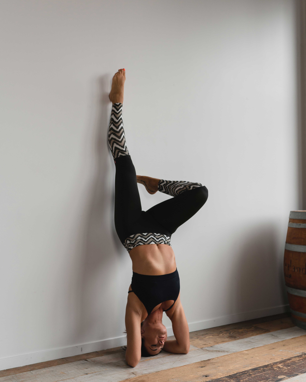Cô gái mặc đồ tập Yoga màu đen thực hiện tư thế trồng cây chuối