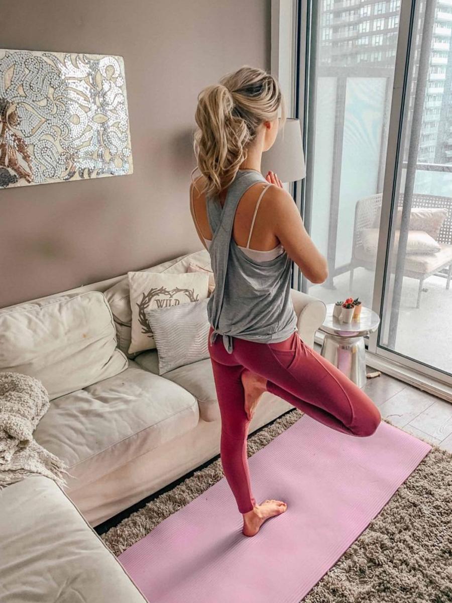 Cô gái mặc áo tank top xám và quần leggings hồng tập Yoga