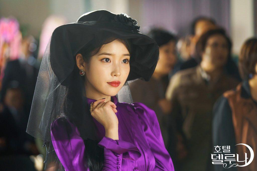 IU mặc đầm lụa tím, đội mũ rộng vành đen trong phim Hàn Quốc Hotel Del Luna