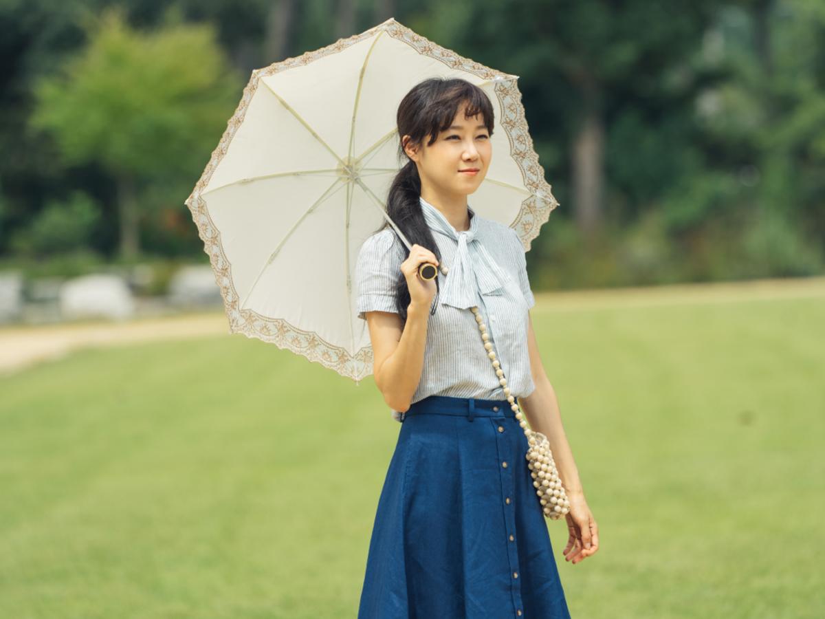 Gong Hyo Jin mặc áo sơ mi xanh, chân váy xanh, cầm dù trong phim Hàn Quốc When The Camellia Blooms