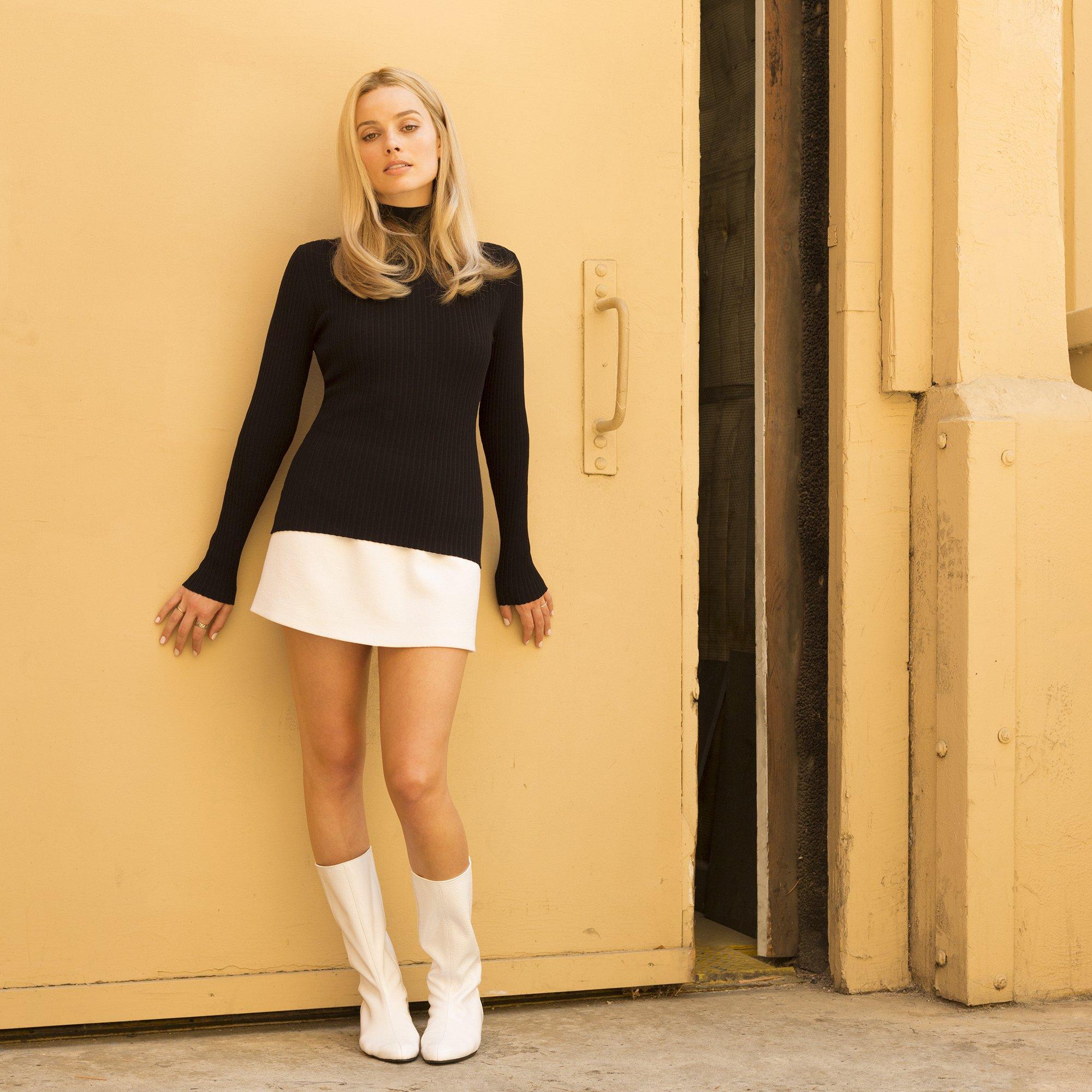 thời trang trong phim once upon a time in hollywood margot robbie áo cổ lọ đen tay dài chân váy trắng boots trắng