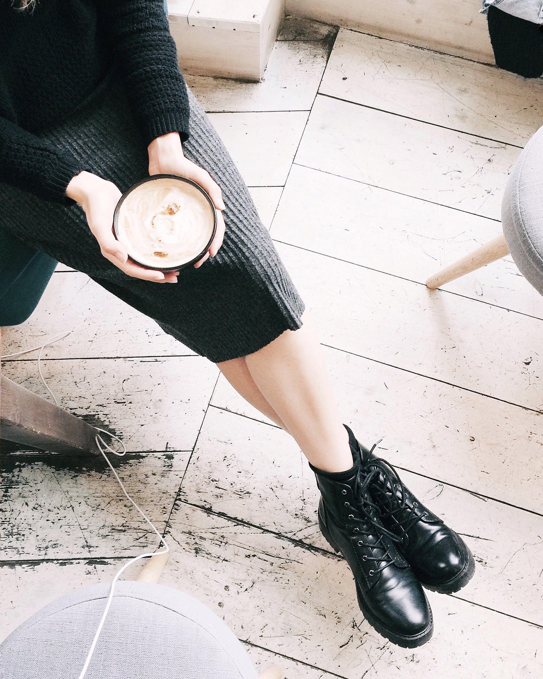 cách vệ sinh giày cô gái cầm ly cà phê mang giày boots da bóng cao cổ