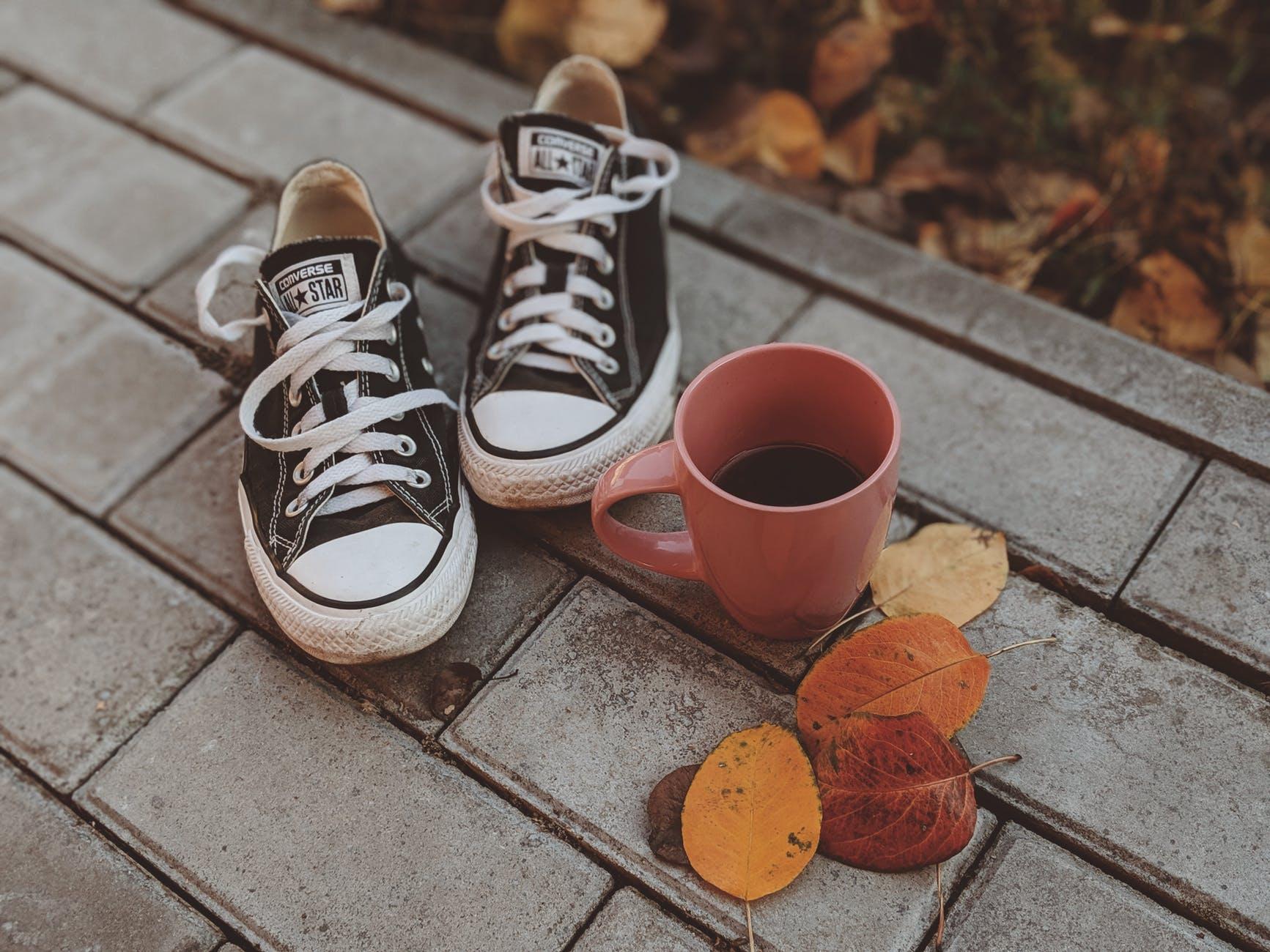 giày converse canvas đen bên cạnh ly cà phê màu đỏ