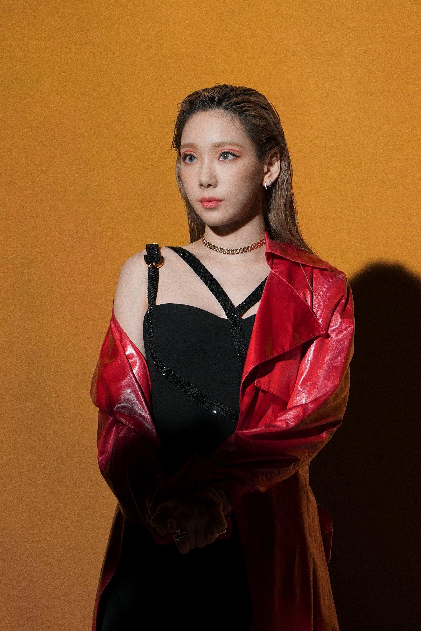 Taeyeon mặc đầm đen, áo khoác da đỏ trong MV nhạc KPOP Spark