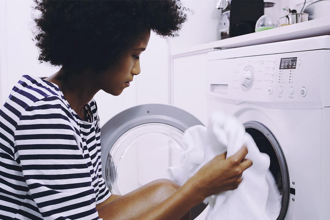 cô gái đang cho quần áo màu trắng vào máy giặt
