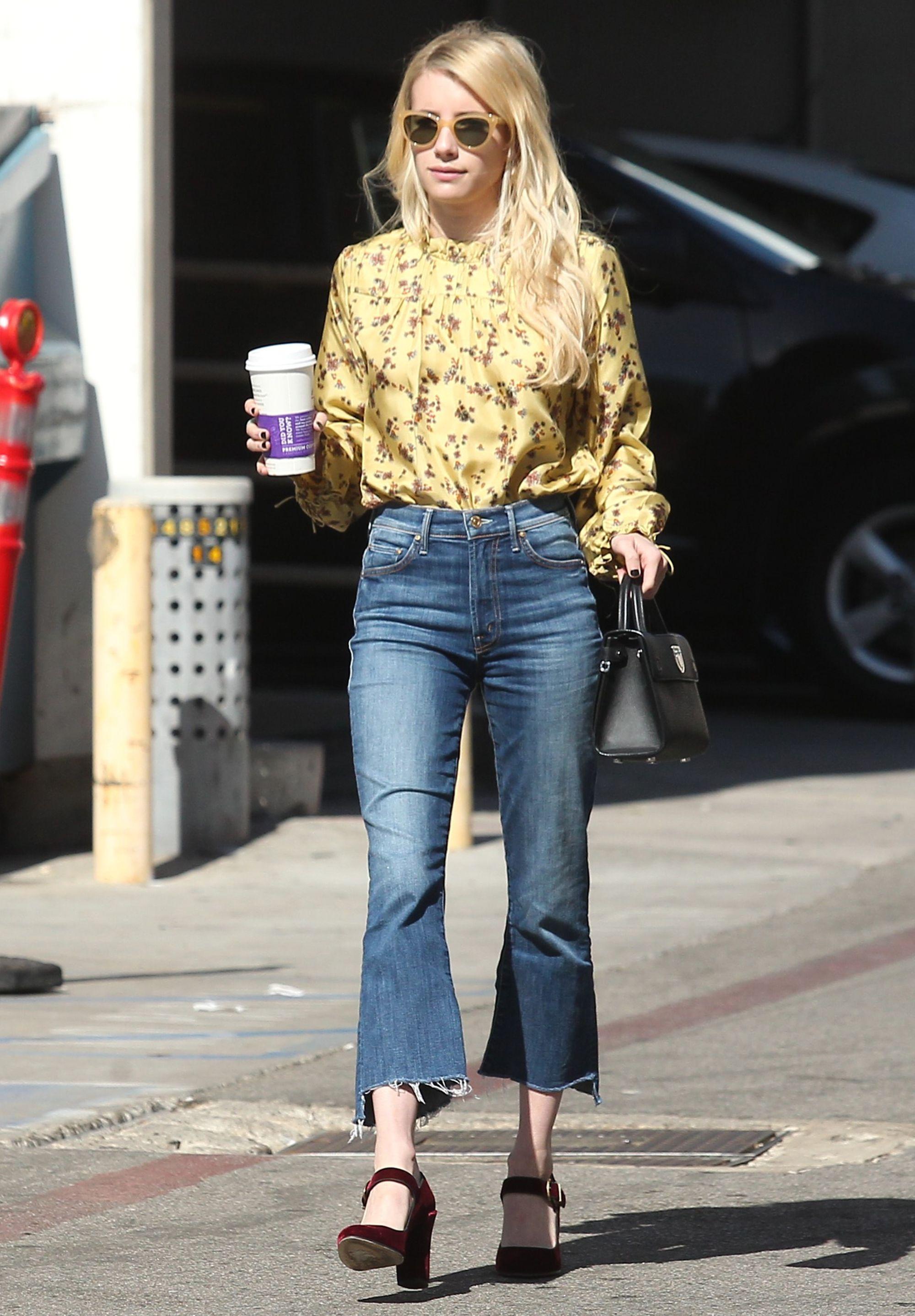 Diễn viên Emma Roberts mặc sơ mi hoa vàng và quần jeans ống loe, mang giày maryjane