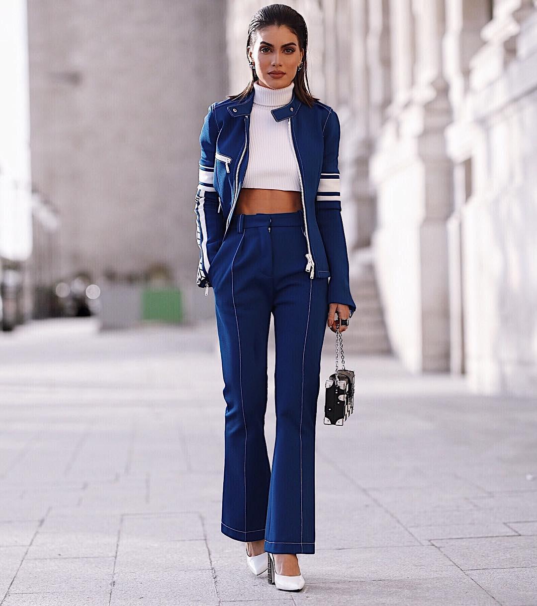 Fashionista Camila Coelho mặc quần ống loe và áo khoác màu xanh dương, mặc áo crop-top trắng, mang giày cao gót