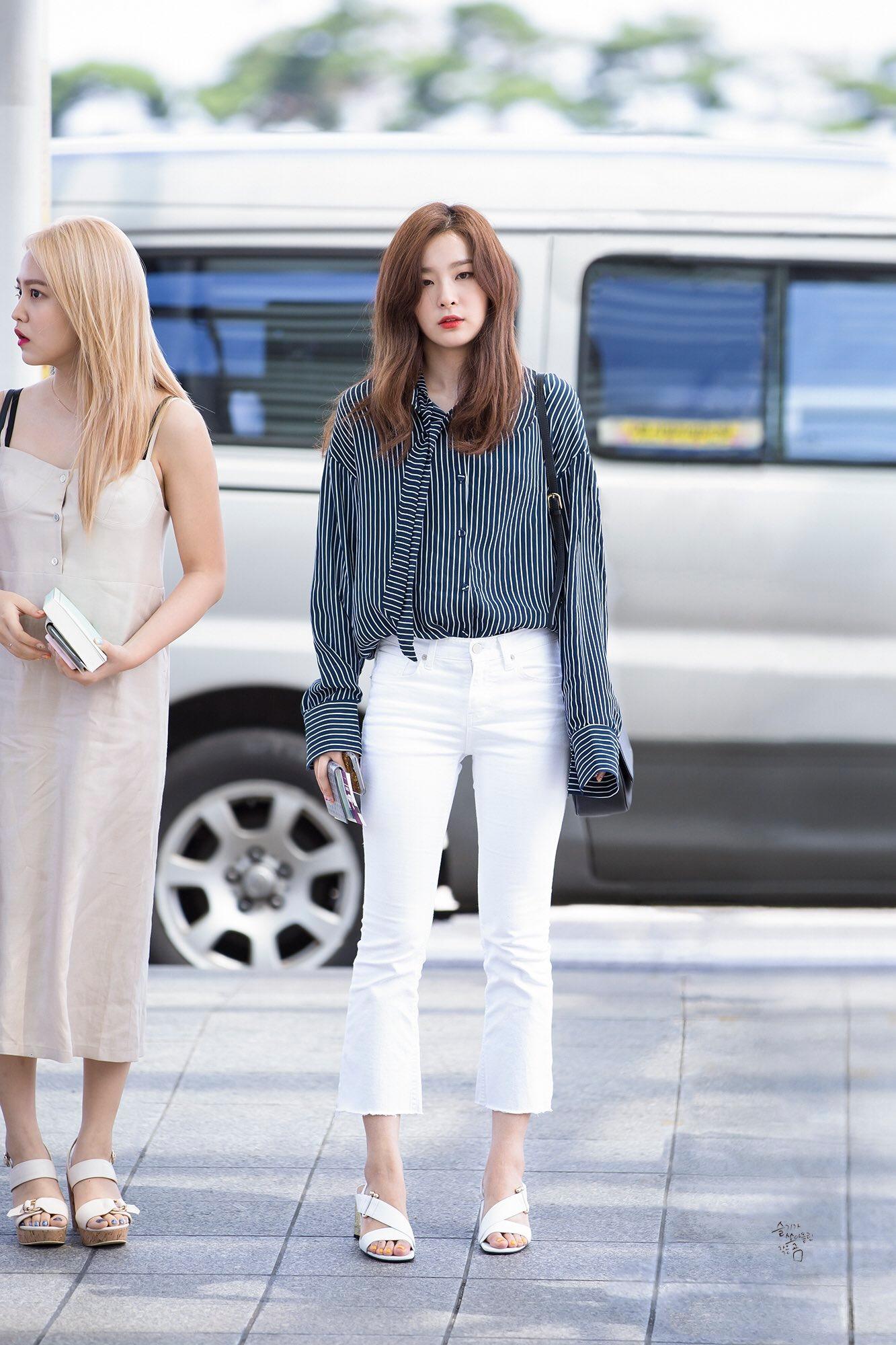 Seulgi (Red Velvet) mặc quần ống loe trắng và áo sơ mi sọc ra sân bay