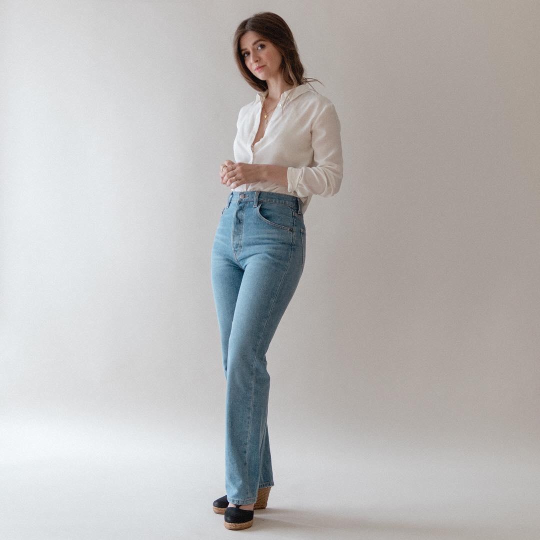 Cô gái mặc quần jeans ống loe, áo sơ mi trắng, mang giày đế xuồng