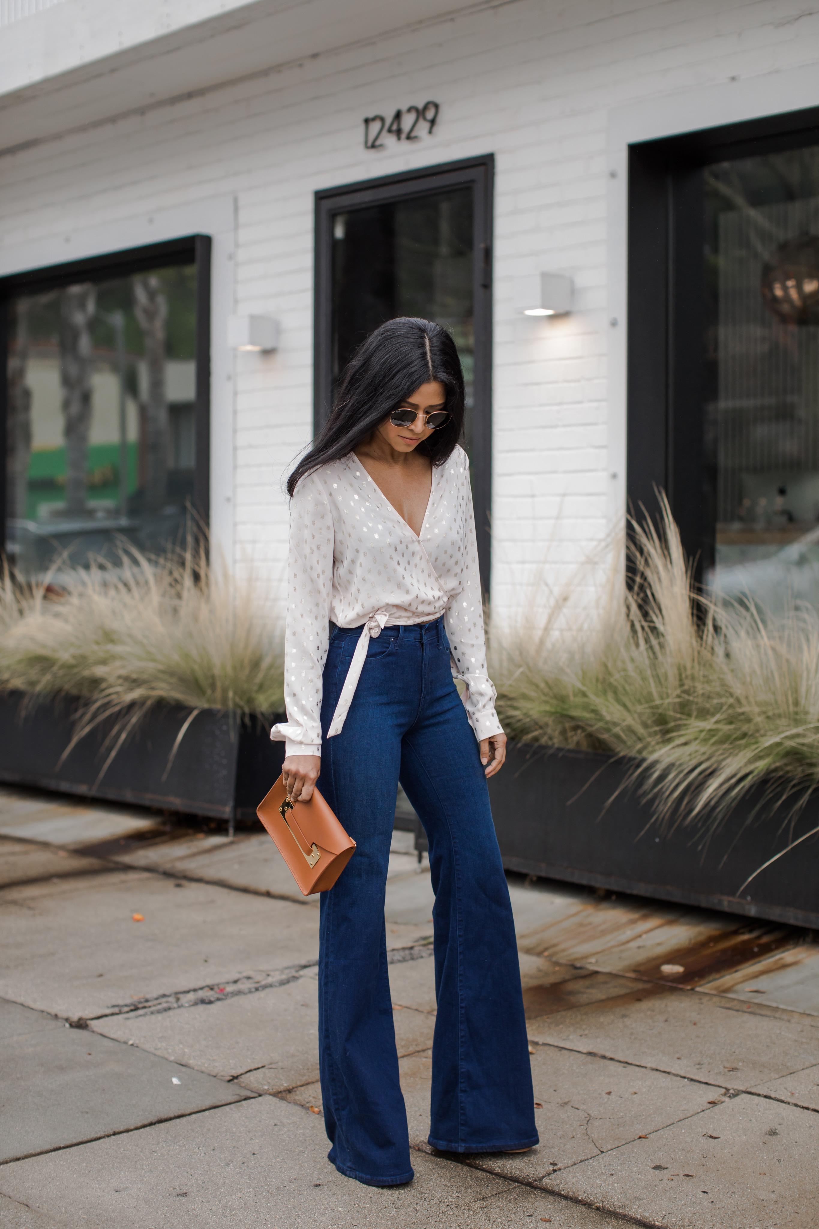 Cô gái mặc quần jeans ống loe, áo cổ chữ V, đeo kính đen, cầm ví da nâu