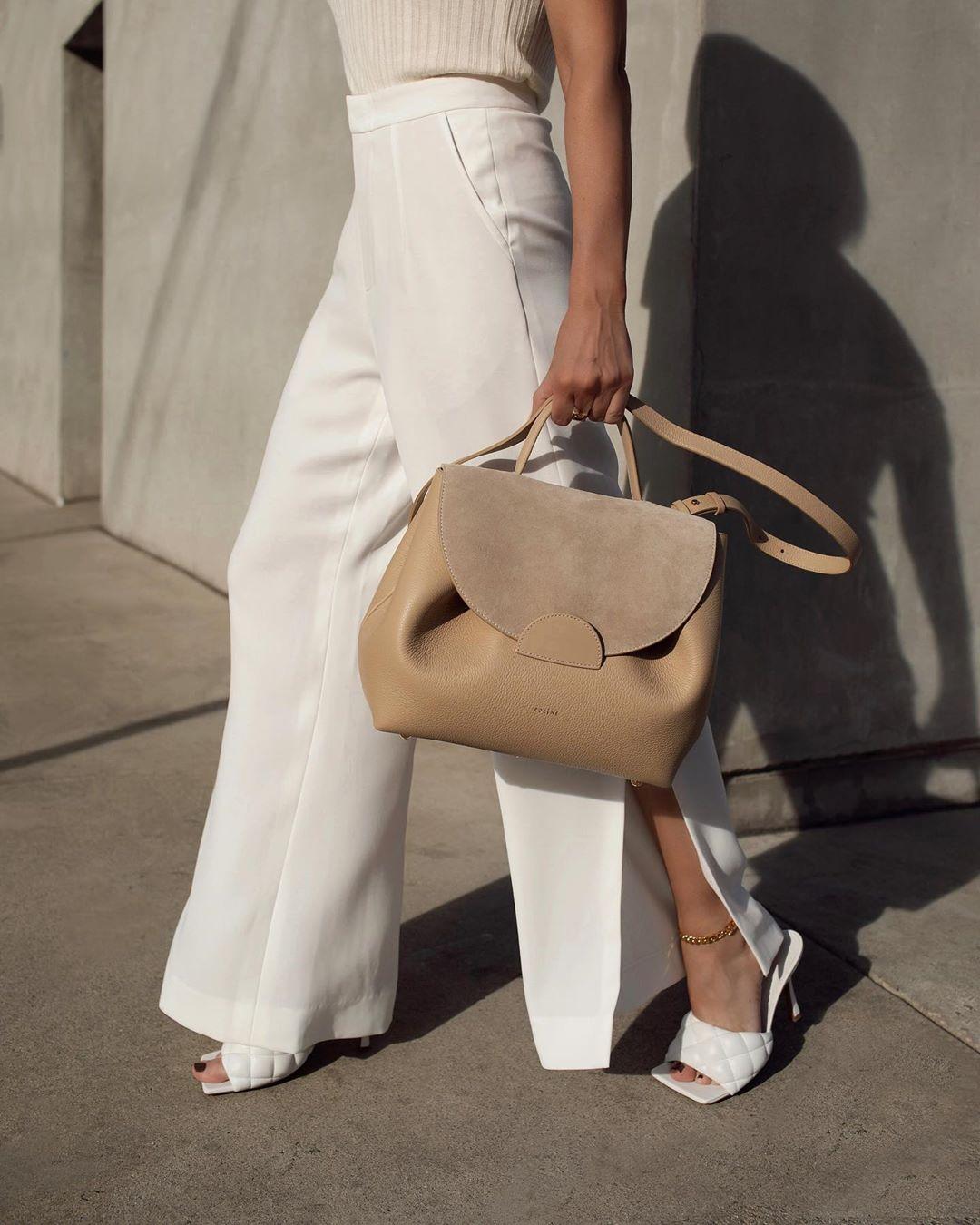 Cô gái mặc quần ống loe xẻ tà màu trắng, cầm túi xách màu nude