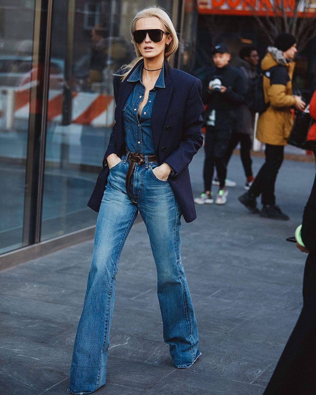 Cô gái mặc quần jeans ống loe, áo jeans và áo khoác blazer