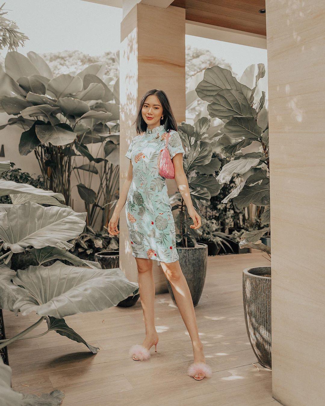 itscamilleco mặc áo sườn xám họa tiết hoa màu xanh mang túi xách màu hồng