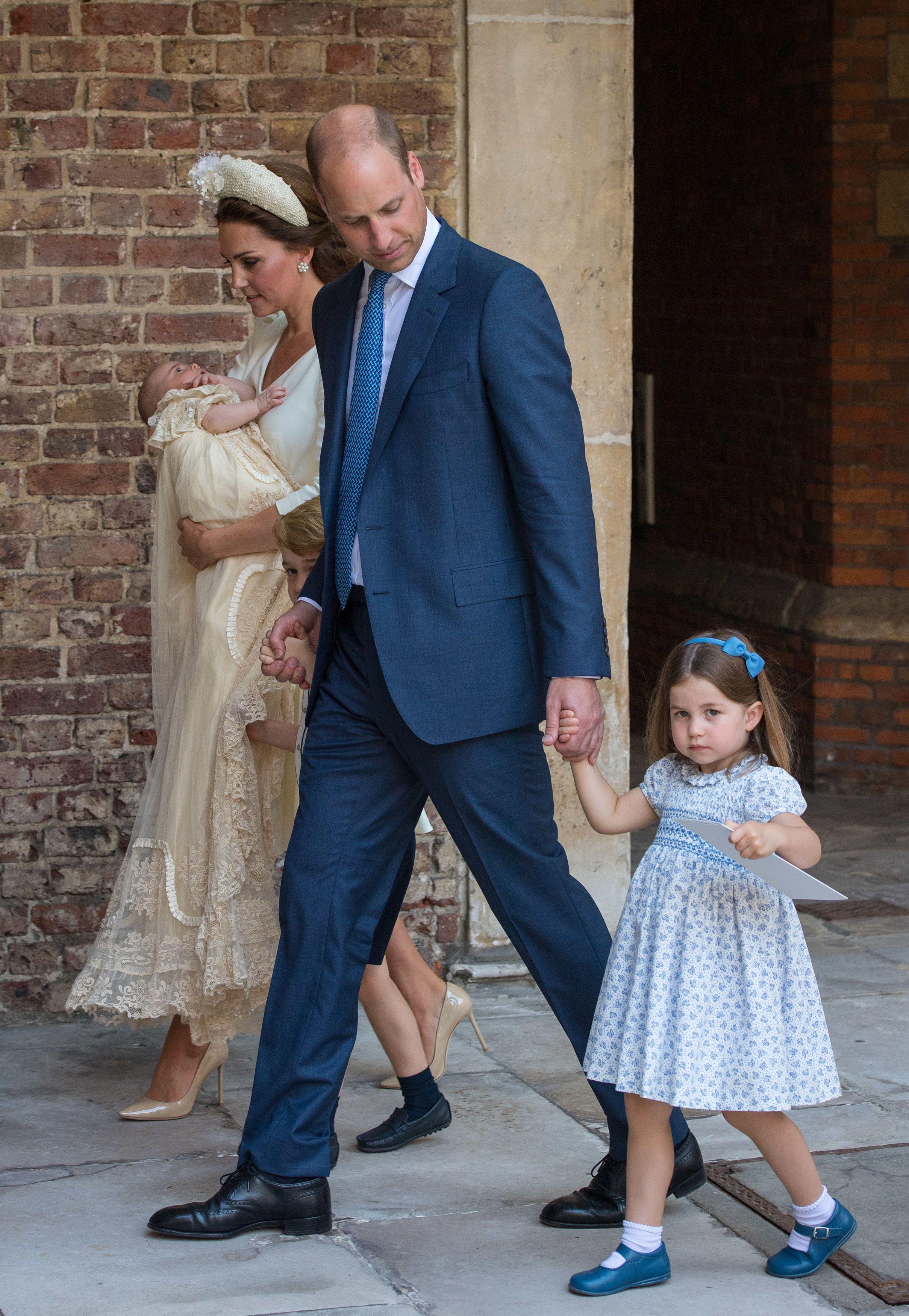 Tiểu công chúa Charlotte mặc đầm hoa nhí mang giày búp bê màu xanh, đi cùng bố mẹ