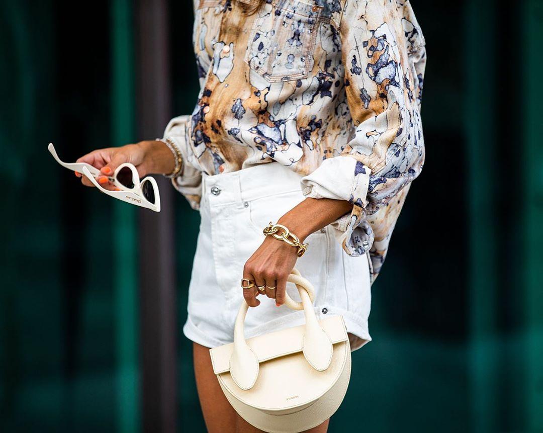 Cô gái mặc áo hoa, quần shorts, đeo vòng đeo tay xích, cầm túi xách và kính mát