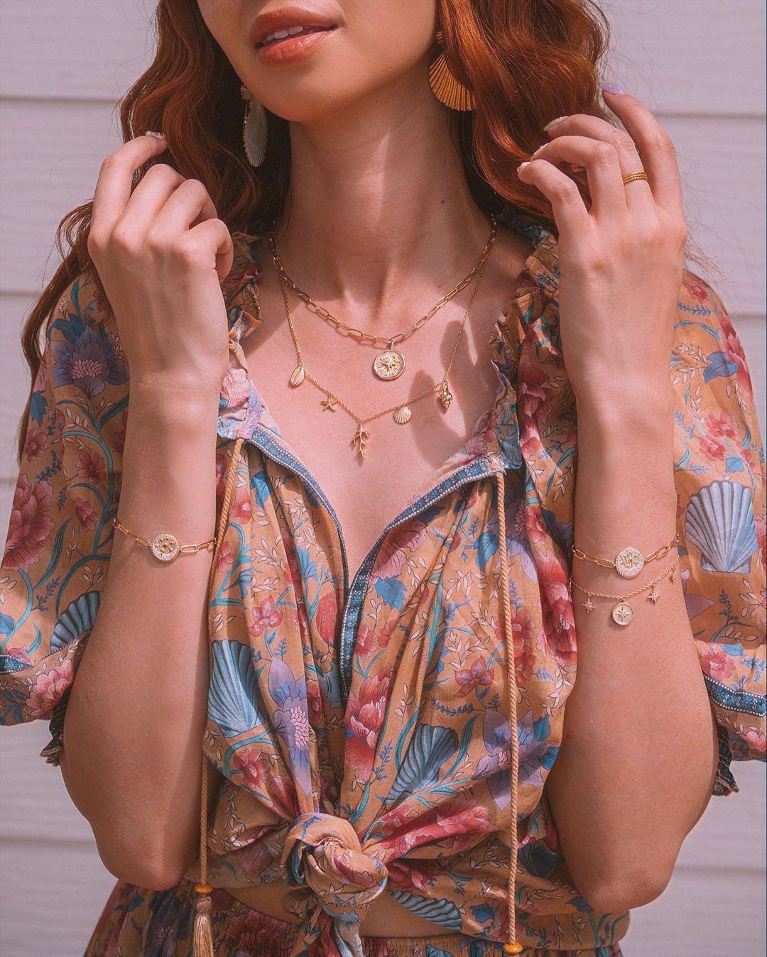Cô gái mặc áo in hoa, đeo vòng tay và dây chuyền mảnh